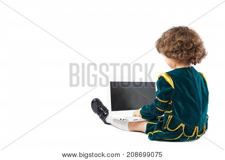 A Curly-haired  Little Boy Dressed As A King Using A Laptop Kept On His Lap.white Background With Sp