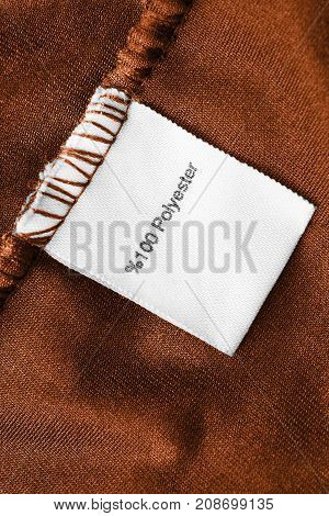 Fabric composition clothes label on brown textile background