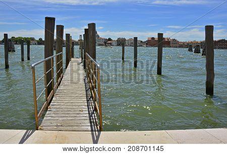 A mooring pier and mooring piles in the Dorsoduro quarter of Venice. The island of Giudecca can be seen across the Giudecca canal.