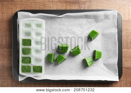 Tray with cubes of frozen vegetable puree on wooden background