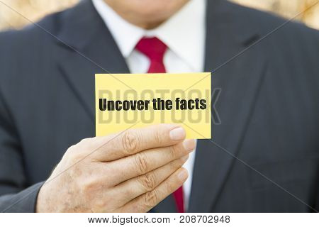 Businessman showing a card with text UNCOVER THE FACTS
