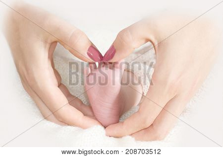 Mother's hands hold the foot of a newborn baby