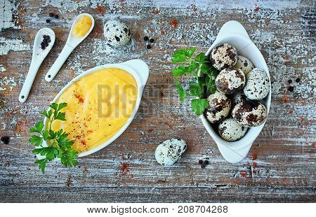 Hollandaise sauce, a basic sauce of the French cuisine, served in a sauce boat and quail eggs on old table