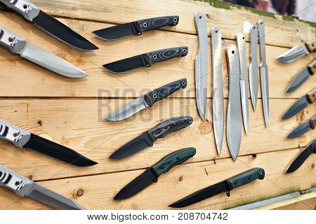 Hunting And Tactical Knives On Wooden Stand In Store