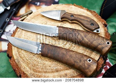The hunting knives on a wooden log
