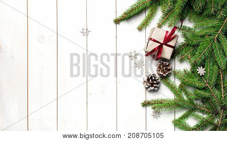 New Year Christmas composition with fir branches of pine cones gift snowflakes snow decorative ribbon. Traditional festive decoration christmas white background