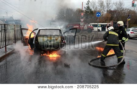 firefighters extinguish a burning car on the street in Russia to 2017