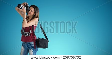 Young woman photographing through digital camera against blue vignette background