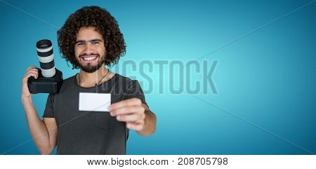 Portrait of smiling photographer showing card while holding camera  against blue vignette background