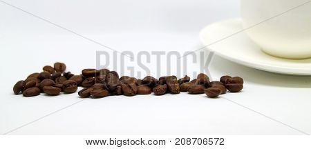 Beams of coffee and white cup on the table. A cup of fragrant coffee for morning vivacity.