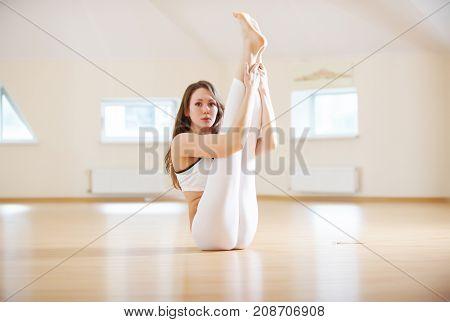 Beautiful woman practices yoga asana Eka Pada Padma Urdhva Mukha Paschimottanasana in the yoga studio.