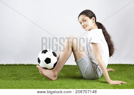 A Beautiful Happy Girl In A Sport T-shirt Is Holding A Soccer Ball On Her Legs. Gray Background