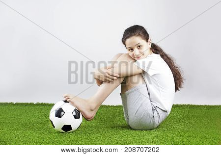 Beautiful Happy Girl In Sports Shirt Sitting On Grass Holding Soccer Ball With Legs. Gray Background