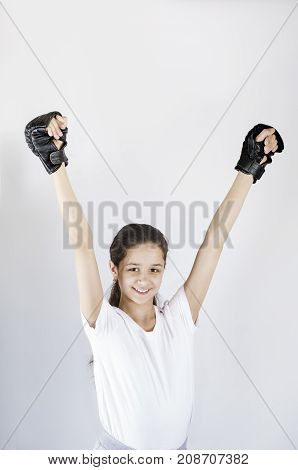Cheerful Little Girl In Black Boxing Gloves With Hands Up Smiling
