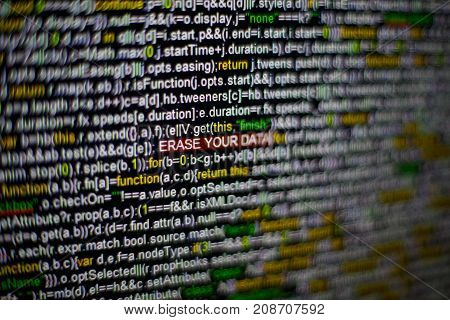 Macro photo of computer screen with program source code and highlighted ERASE YOUR DATA inscription in the middle. Computer script on the screen with virus in it. Cyber security concept.