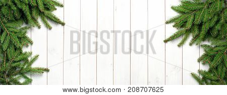 Christmas fir tree branches on a white wooden background. New Year's background, holiday, christmas, green branches top view with copy space.