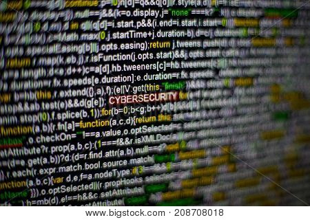 Macro photo of computer screen with program source code and highlighted CYBERSECURITY inscription in the middle. Computer script on the screen with virus in it. Cyber security concept.