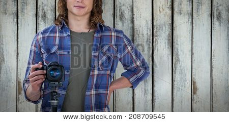 Portrait of young confident photographer holding camera against wood background