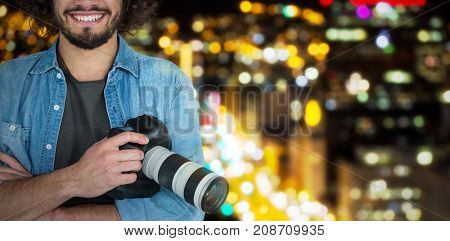 Portrait of smiling male photographer holding digital camera  against defocused image of illuminated buildings