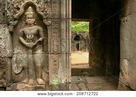 Entrance to inner sanctuary of Ta Som temple in ancient Angkor in Cambodia guarded by armed dvarapala, a temple guard.