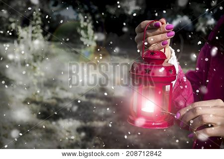 on a snowy winter evening a girl lights the candle of a Christmas red lantern