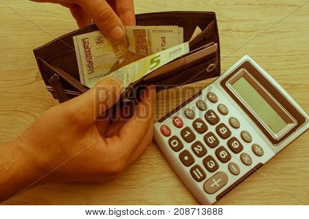 Hand holding dollars and wallet. Wallet with cards and money. It was a busy month. Enough money for proper vacation - Retro color