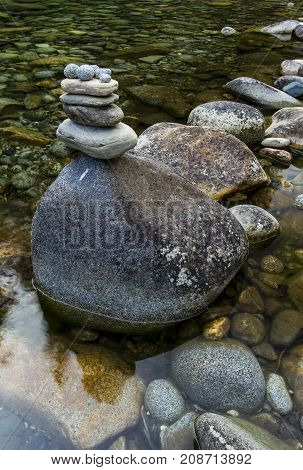 Rocks stacked upon one another in a calm stream in Canada.