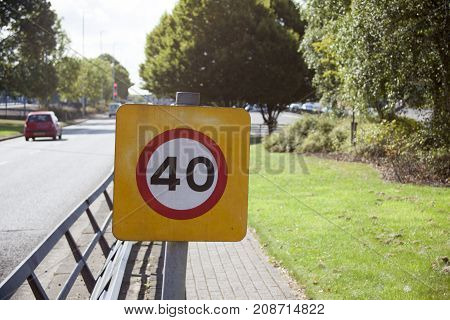 Warning sign or road sign for the maximum speed limit next to the busy road