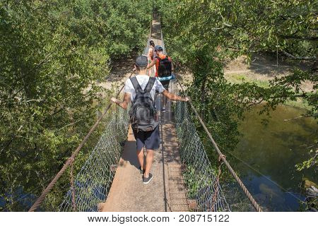 Trekking together. Active hikers. Travelers travel on the artificial roadway of the suspension bridge. Tourist at the spring