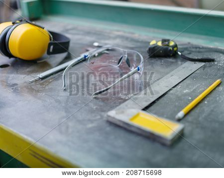 Tools of the carpenter close-up on a gray background of the table calliper, roulette, glasses, corner, pencil