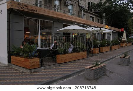 Yalta, Crimea - 11 July, People in the open evening cafe, 11 July, 2017. Streets and embankments of the seaside city of Yalta.