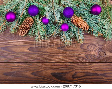 Winter concept of a green spruce branch on a brown wooden background with cones and toys