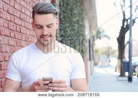 Latin Man Typing On His Phone.