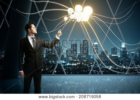 Businessman holding light bulb balloons on in empty concrete interior with panoramic night city view. Idea concept. 3D Rendering