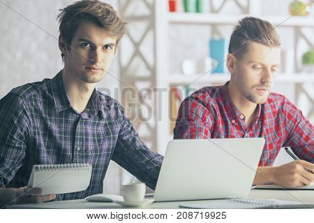 Portrait of two attractive european boys working on project at workplace. Team work concept