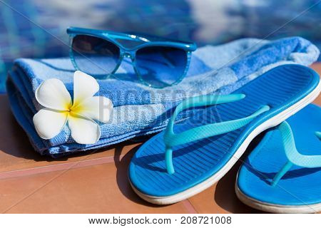 Blue Slippers, Sunglasses And Towel On Border Of A Swimming Pool