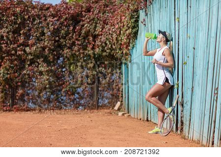 Pretty young tennis player on a blue background drinking water with closed eyes. Side view. The concept of sport.
