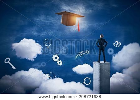 Back view of young businessman standing on concrete pedestal and looking at abstract sky with glowing mortarboard. Graduation concept