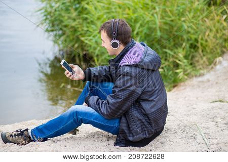Young man in excellent spirits sits on the river bank with a phone and listens to music
