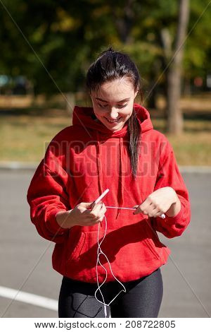 Sporty girl in red uniform looking for music on the phone for jogging