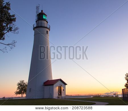 Lighthouse Sunrise. Soft sunrise colors and illuminated beacon of the Fort Gratiot Lighthouse in Port Huron, Michigan. Fort Gratiot is the oldest active lighthouse in the state of Michigan.