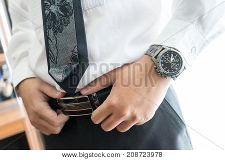 Man buttons belt to preparation for wedding ceremony or for business work