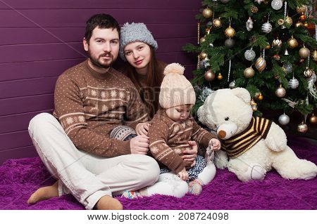 Little girl and her parents portret with christmas decorations indoors.