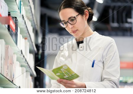 Low-angle portrait of an experienced female pharmacist checking the medical prescription of a pharmaceutical drug, while working in the interior of a modern drugstore with various products