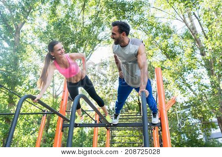 Low-angle view of a young fit woman and her partner smiling while practicing plank exercise during outdoor couple workout in a calisthenics park