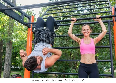 Happy fit young woman and her workout partner doing crunches and vertical leg raises for abdominal muscles outdoors in a modern calisthenics park