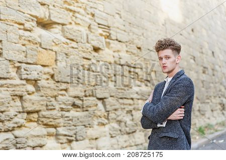 Businessman in gray coat. Standing against the wall background, hands clasped. The concept of career and entrepreneurship. Close-up.