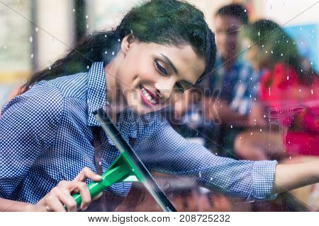 Indian girl cleaning windows with squeegee, close