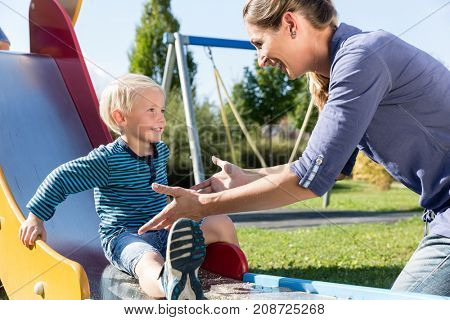 Woman and little boy chuting down slide at playground outdoors