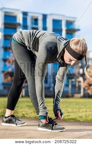 Full length of an active young woman tying the shoelaces of her sport shoes, while wearing trendy workout outfit in a sunny day in the park